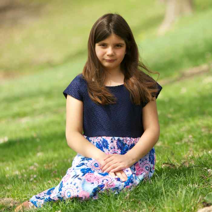 Girl with shirt and skirt sitting in green grass