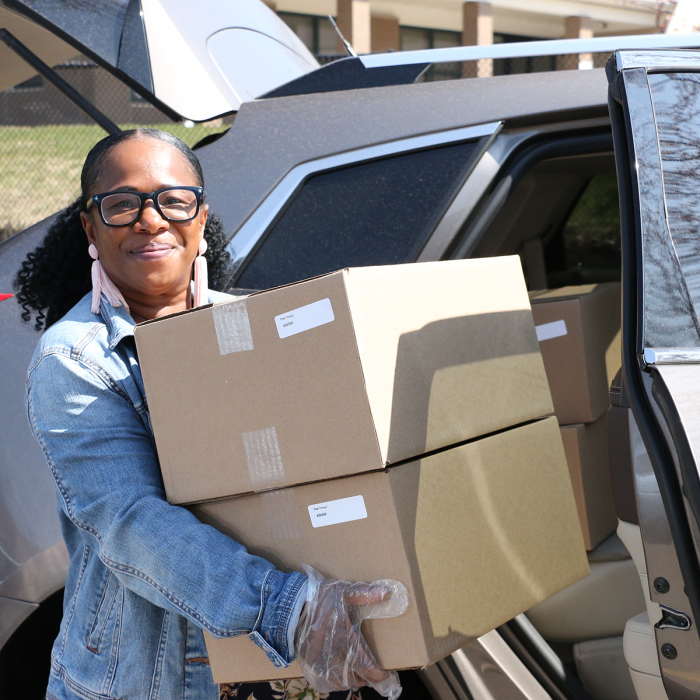 Chalese Knight, a Wilder supportive housing team member, unloads food boxes from her car
