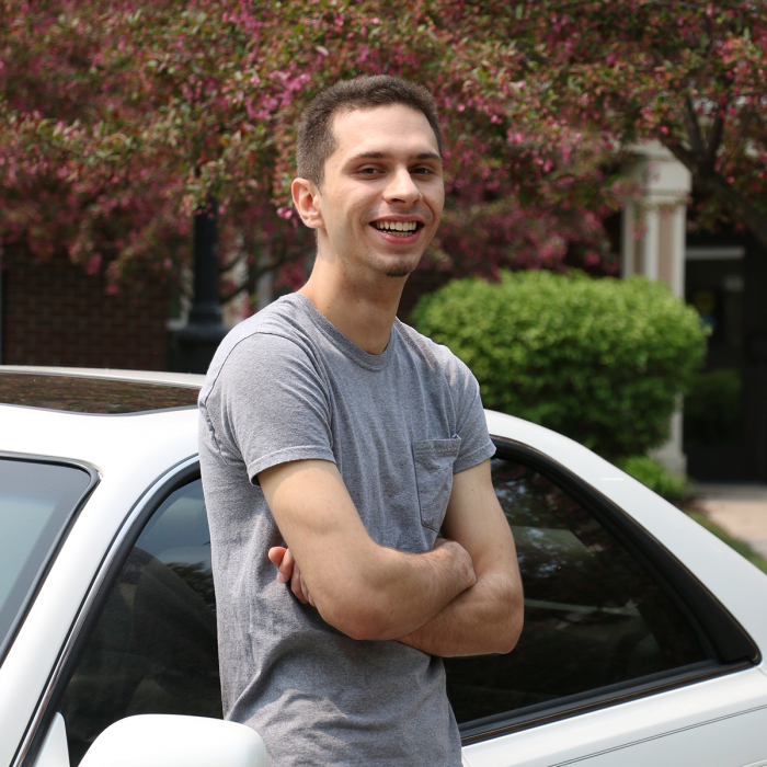 Sebastian Dina, participant in Wilder supportive housing services, poses in front of his car outside Lincoln Place supportive housing development in Eagan, Minnesota