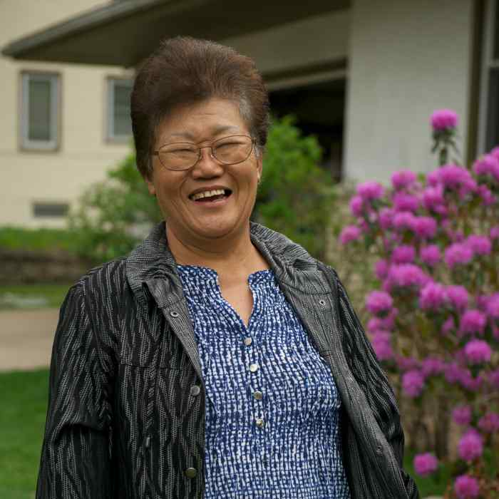 Smiling older Asian woman standing in front of a house and flowering bush