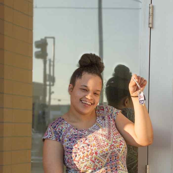 Youth smiling and holding house keys, youth housing site in saint paul, prior crossing resident