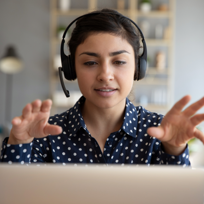 A woman wearing a headset talks as she faces a laptop. Her hands are raised as she talks.