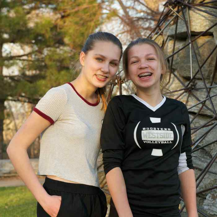 Two smiling teen girls standing outside