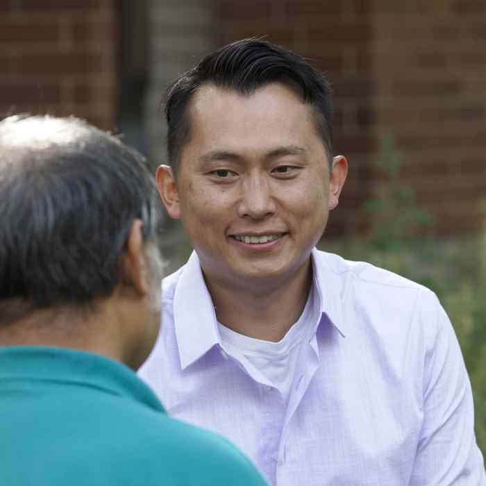 Smiling Asian American male, Asian Peer Specialist talking to older adult male, community mental health and wellness services, mental health recovery