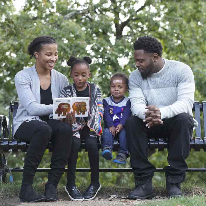 African American family sitting on park bench, african american mother and father with daughter and son, child development center family, minnesota community childcare, preschool family in saint paul minnesota