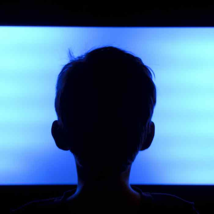 Child silhouette in front of blank TV screen