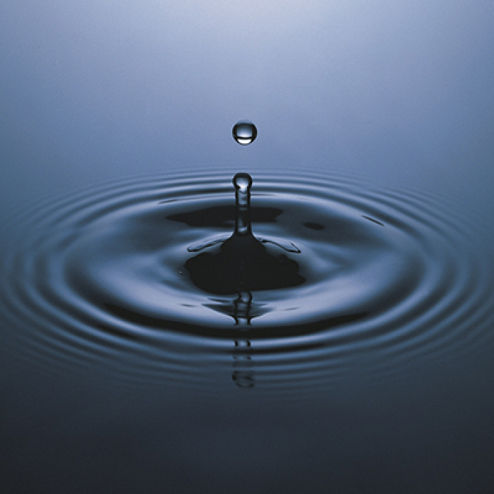 Close-up of a water droplet creating ripples.