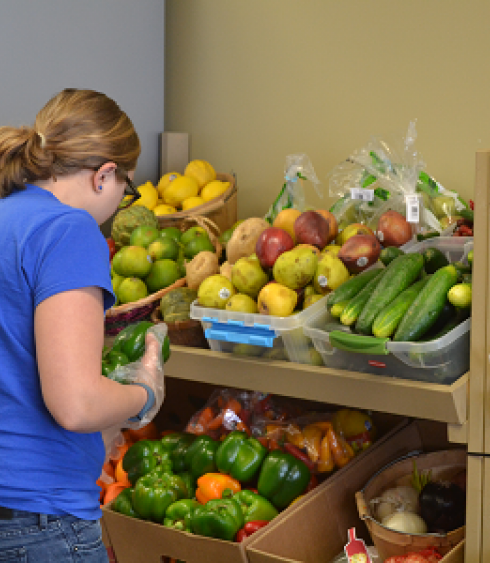 A woman faces and selects from shelves of fruit and vegetables.