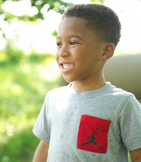 Young boy smiling outside
