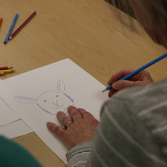 Older adult drawing a rabbit in a Wilder's Adult Day Health Program activity at the Wilder Community Center for Aging in Saint Paul, Minnesota.