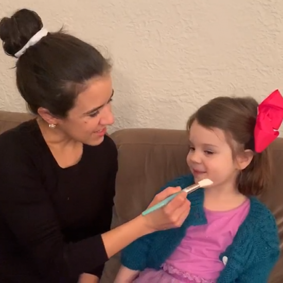 Mother painting imaginary picture on daughter's face during play therapy