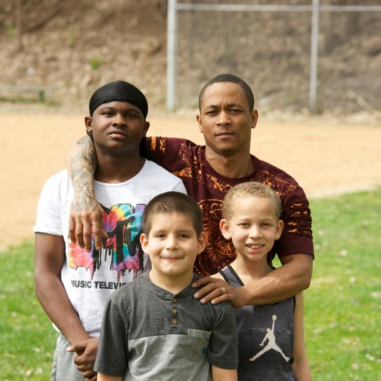 Man standing with his arms around three young boys in a park