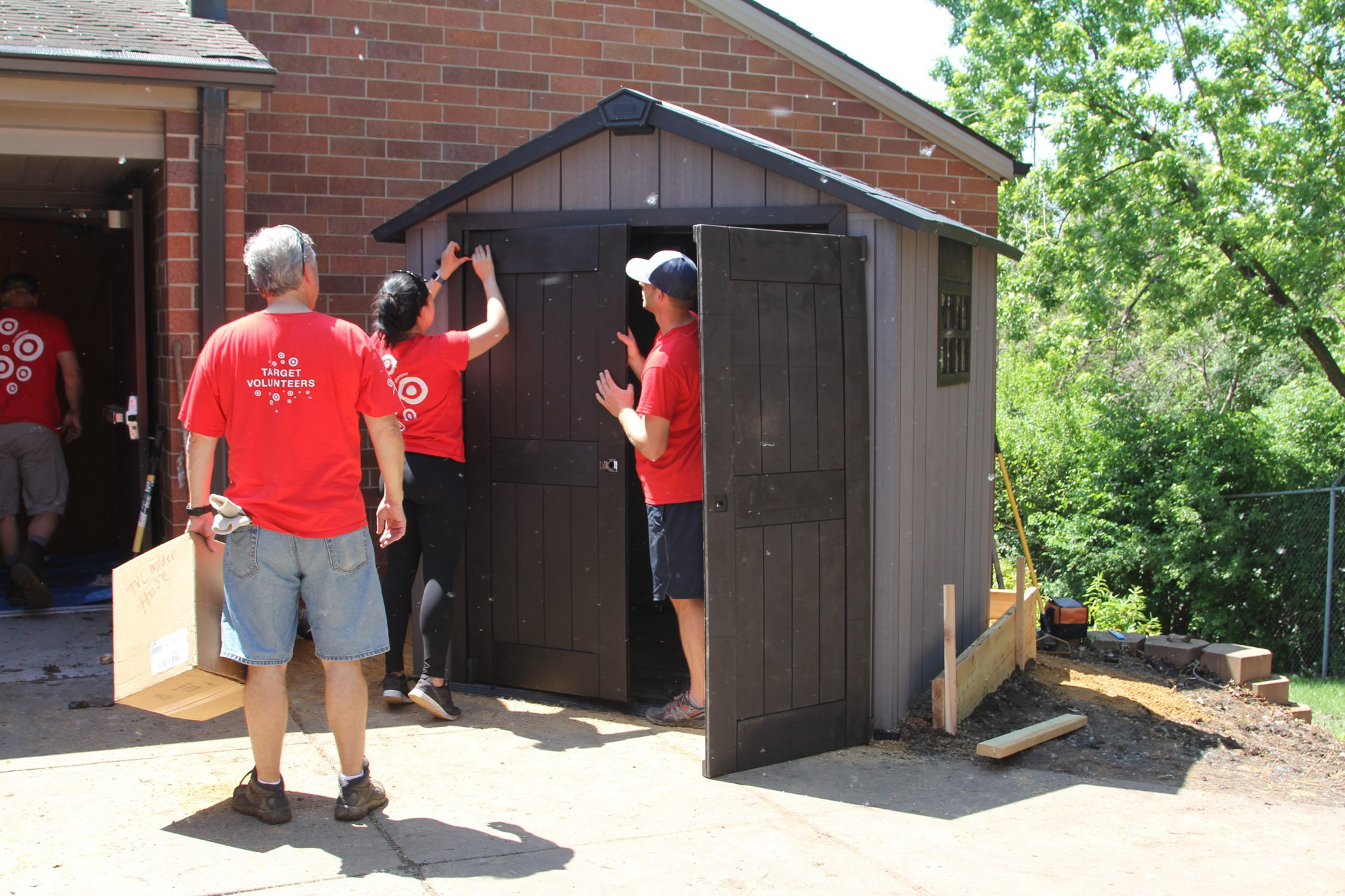 Volunteers work on a new shed outside the Wilder Center for Social Healing