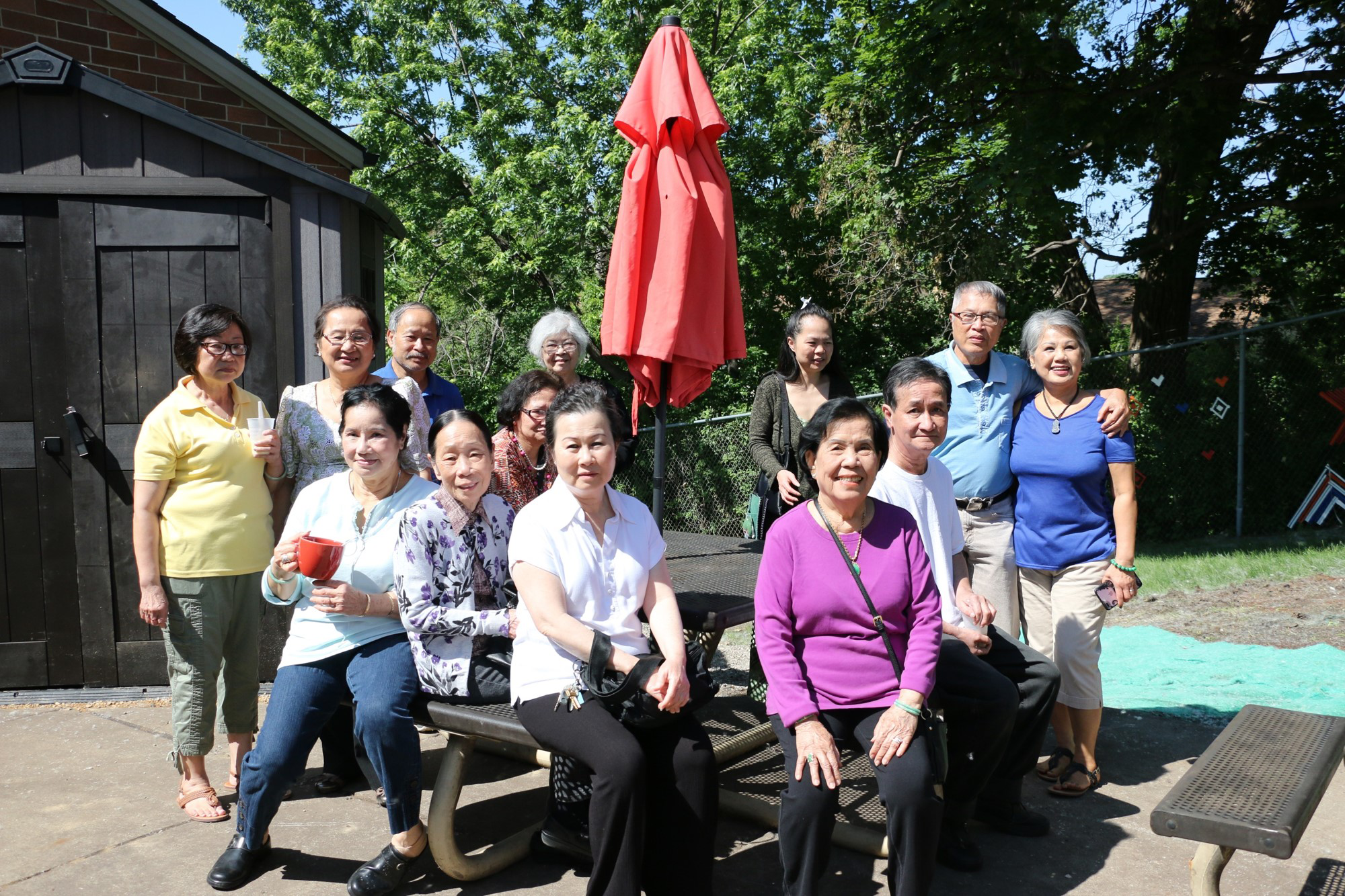 Members pose at a table near a donated shed outside the Wilder Center for Social Healing.