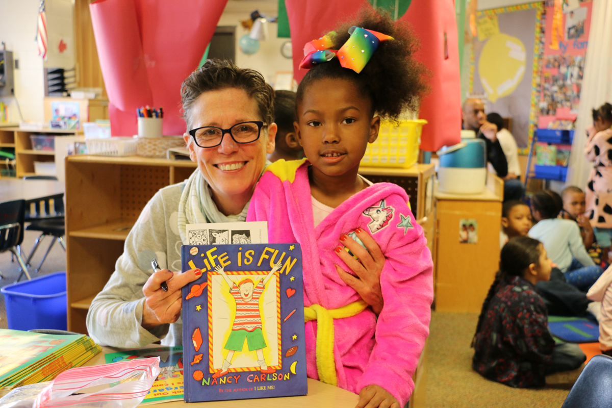 Nancy Carlson and Wilder Child Development Center student with book