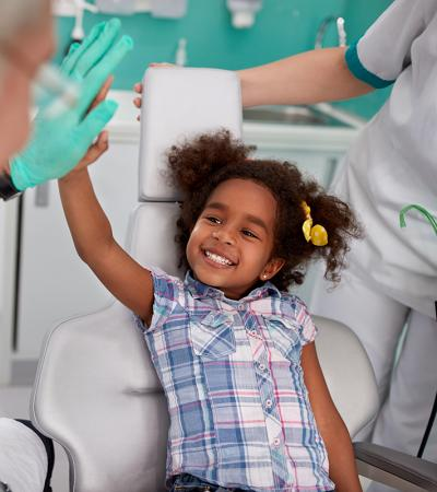 A young girl, sitting in a dentist's chair, smiles and gives a high five to a man in soft focus.