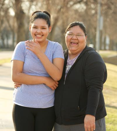 Daughter and mother standing in park laughing