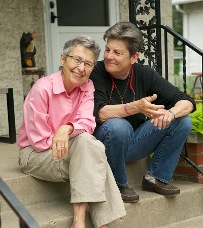 Two women sitting on front steps of a house smiling