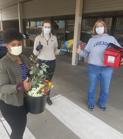 Meals on Wheels volunteers with masks and flowers at Wilder