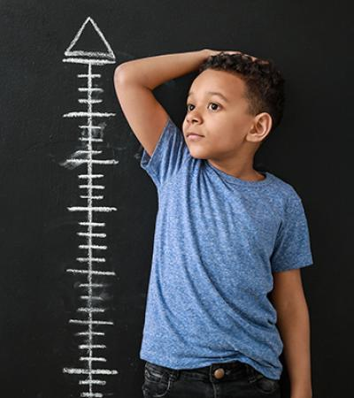 A boy stands next to wall chart measuring height.