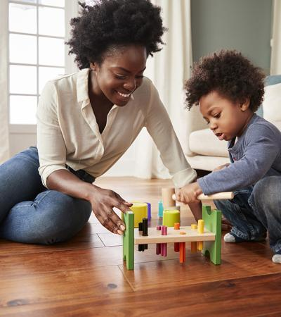 A woman and a toddler sit on the wood floor of a home and play with multi-colored toys.