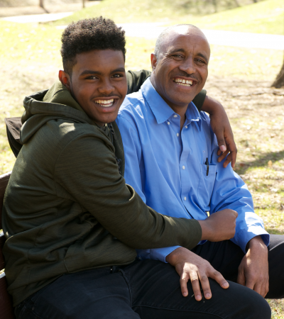 Father and son smiling sitting on park bench