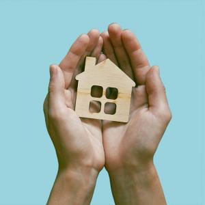 A pair of hands hold a small cutout of a wood house.