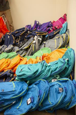 Piles of backpacks to deliver to children served by Wilder