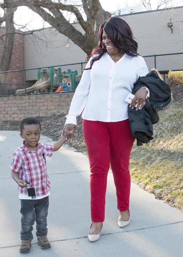 parent and child standing outside preschool, black mother and son at childcare center, child development center family