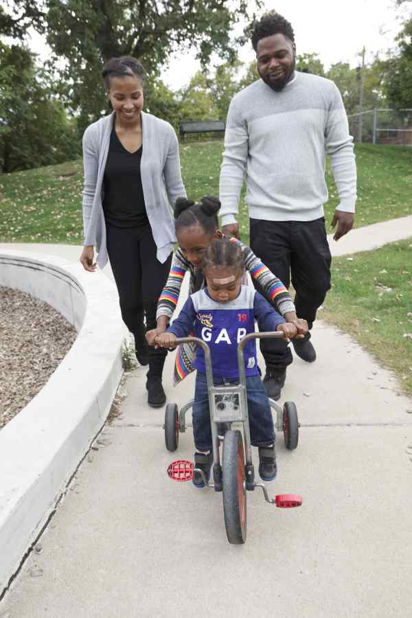 african american family in saint paul minnesota, african american mother and father with daughter and son on bicycle, wilder child development center family, minnesota community childcare, preschool family