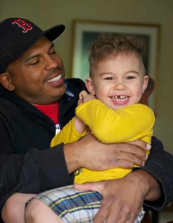 Father wearing baseball cap holding smiling young boy in his arms